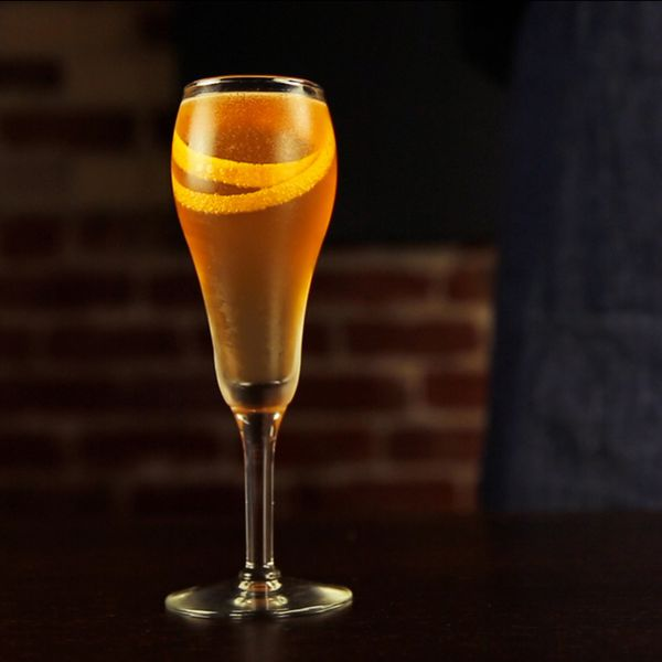 Seelbach Cocktail in a flute with a long orange twist wrapped inside the glass