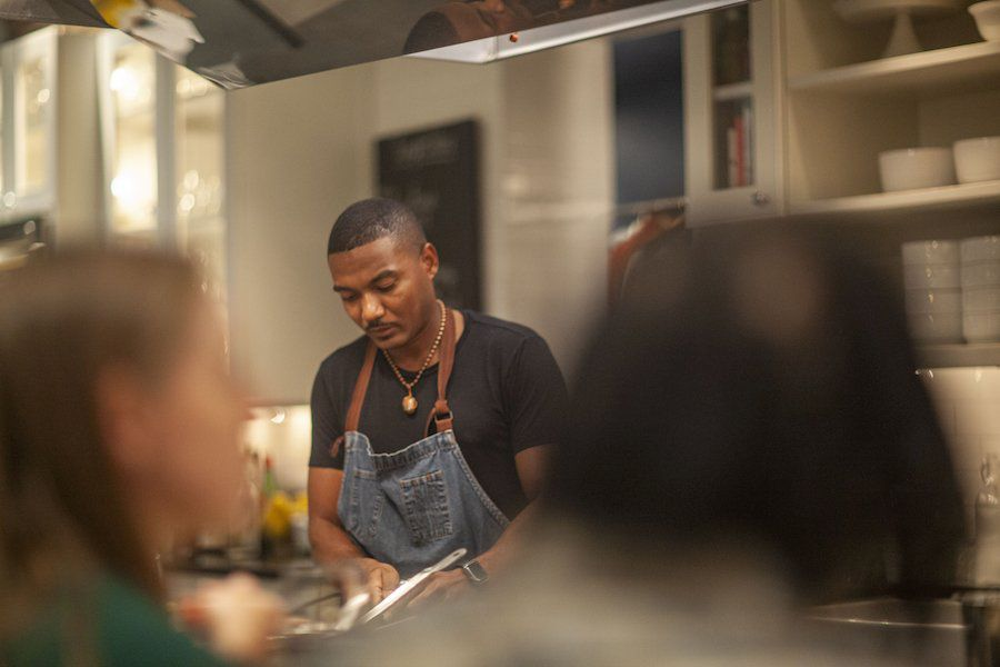 A chef in a black T-shirt and a denim apron preparing dinner for a small group of guests