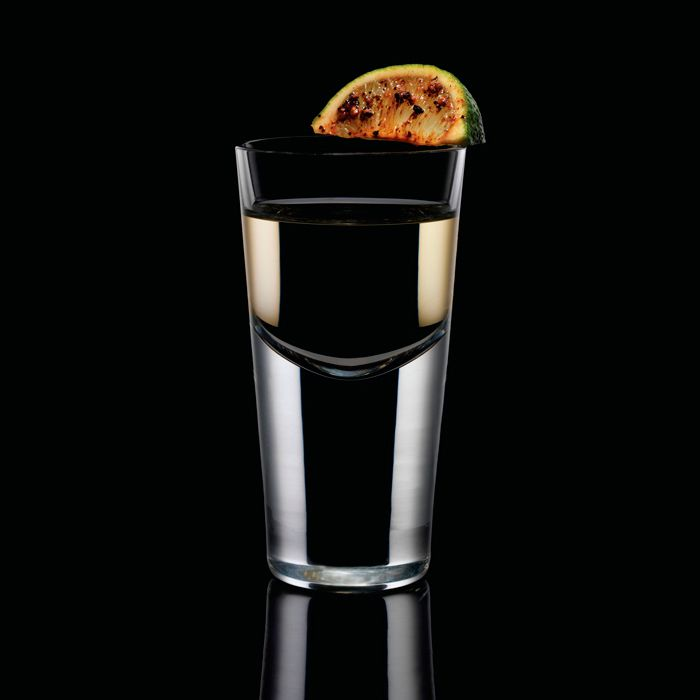 A dramatically lit, thick-based shot glass is set against an all-black background. It's filled with a pale golden liquid, and a lime wedge coated in pepper and bitters rests on the lip.