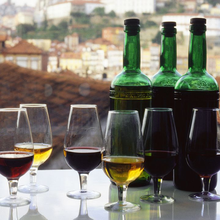 Port wine in glasses against a rooftop view of a Portuguese neighborhood and its terracotta-shingled roofs