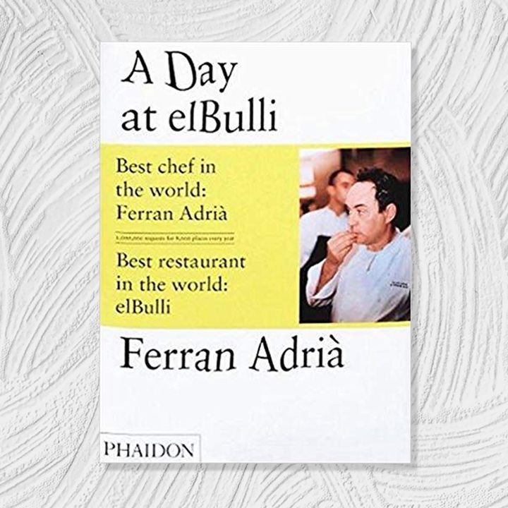 A Day at elBulli cover, white background with yellow color block and distorted black text alongside right-aligned photo of chef and author