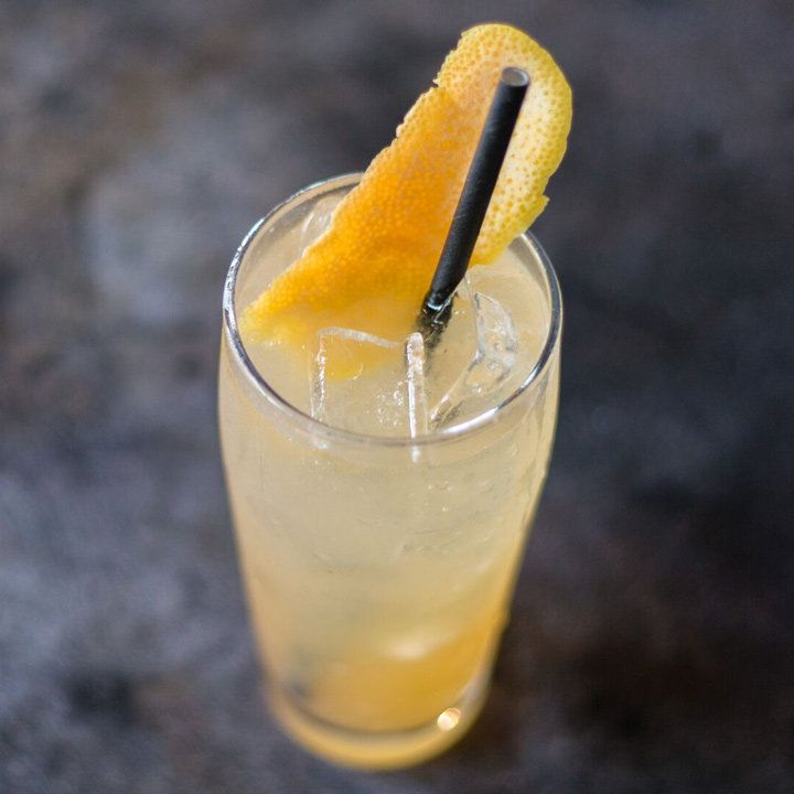 A top-down shot of a golden-hued drink filling a highball glass, with a black paper straw and a long grapefruit peel garnish. The background is charcoal colored.