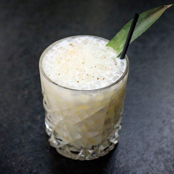 A creamy, light yellow batida in a rocks glass with an allover prism-cut design