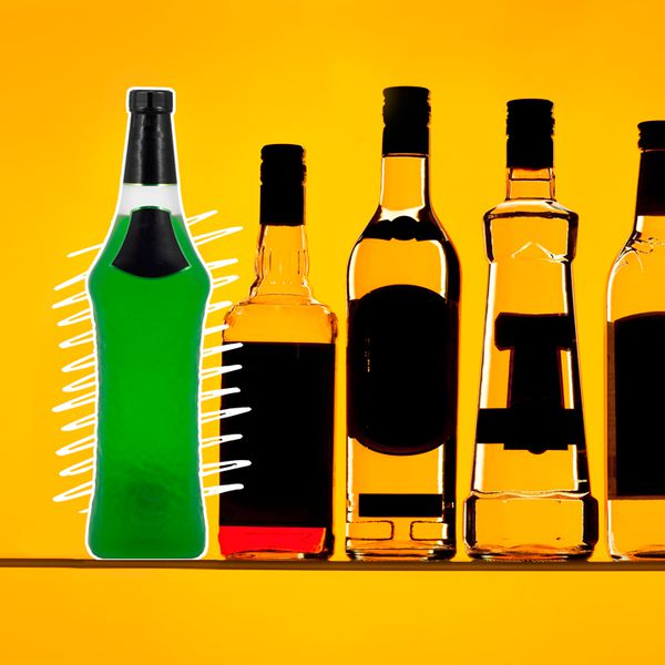 A vividly green bottle of Midori sits over zig zag white lines and a golden backdrop. Next to it are array a number of other liquor bottles, their labels darkened out