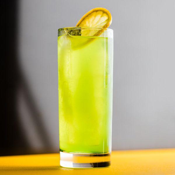 Bright green Midori Sour cocktail with a lemon wheel garnish