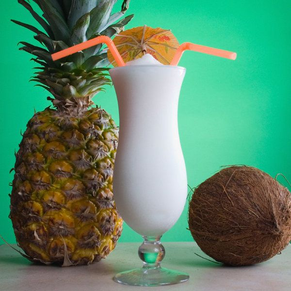 A tall, curved Hurricane glass is flanked by a pineapple to its left and a coconut to its right. The bright white slushy drink is topped with two straws and a paper umbrella, and sits against a bright green backdrop.