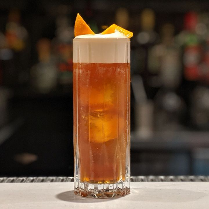 A tall, chunky collins glass sits on a bar top, and holds a dark amber liquid and a few large ice cubes. On top, a curved orange zest floats on a thick layer of foam.