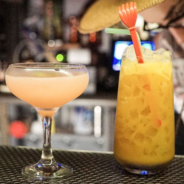 A light pink cocktail in a coupette next to a highball containing a shaken orange cocktail on crushed ice and garnished with an orange swizzle stick and a green straw