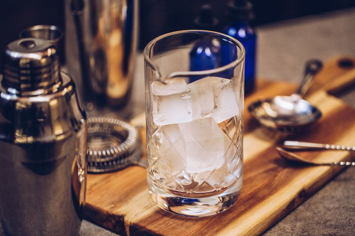 Centered in the photo is a clear mixing glass filled with large ice cubes. The mixing glass is on a wooden cutting board surrounded by other bar accoutrements including bar spoons, strainers, and shaker tins.