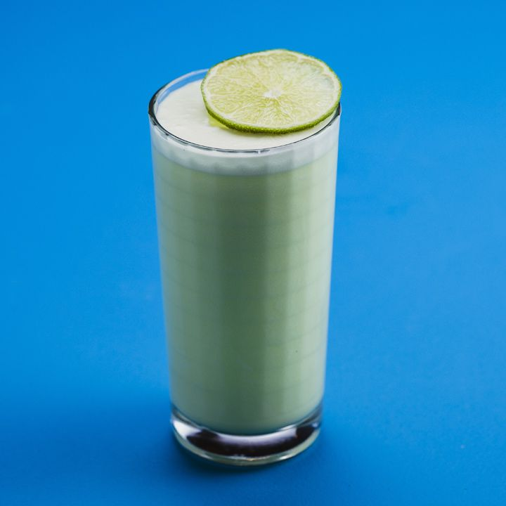 On a solid blue background, a faceted Collins glass holds a pastel-green drink, topped with foam and a fresh lime wheel resting on the lip of the glass.