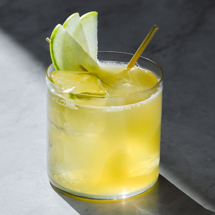 Apple Business cocktail with three skewered apple slices and a straw