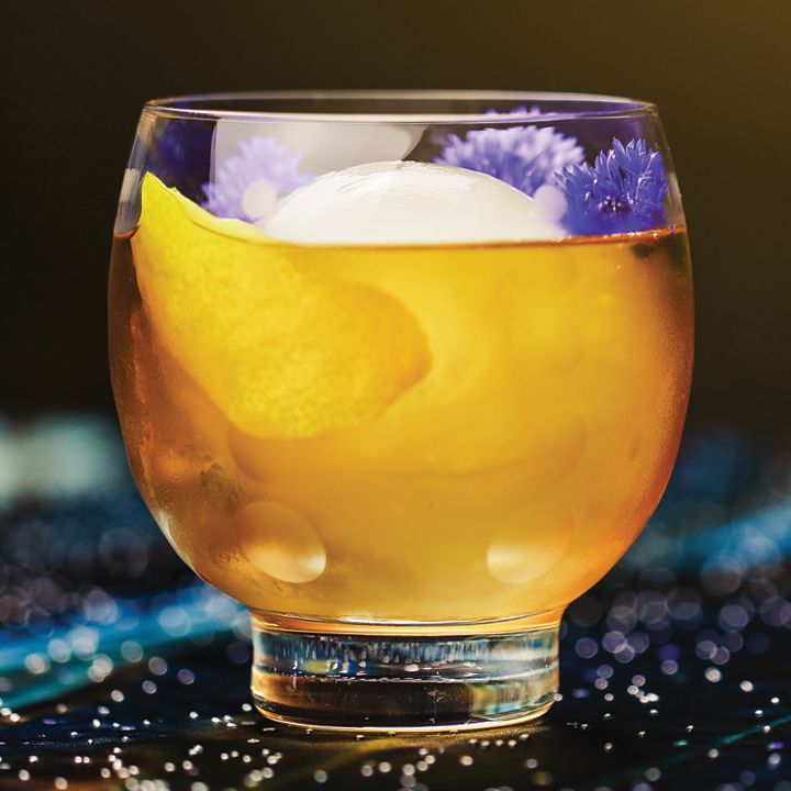 Guinan's Negroni cocktail in a round-bowled double rocks glass, served over an ice sphere and garnished with a lemon peel and purple flowers