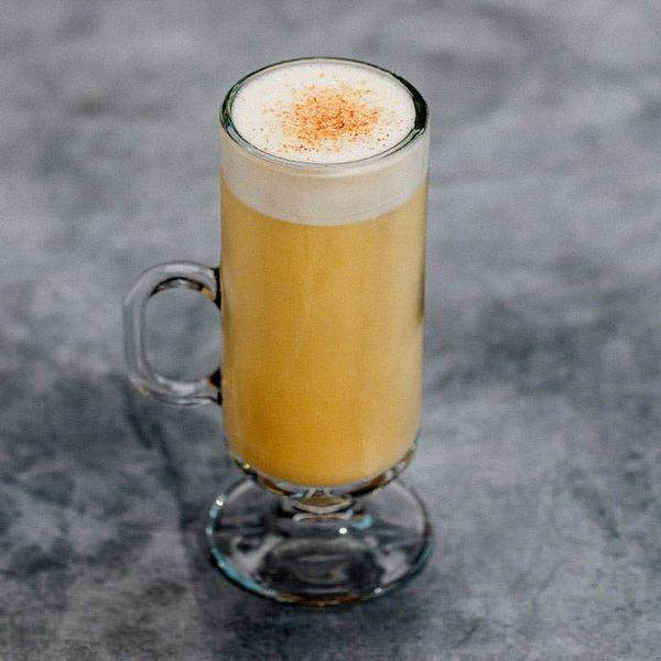 A tall, thin Irish Coffee mug rests on a dark gray marbled surface. The glass mug holds a pale gold drink with a thick layer of white foam, dusted with nutmeg, at the top.