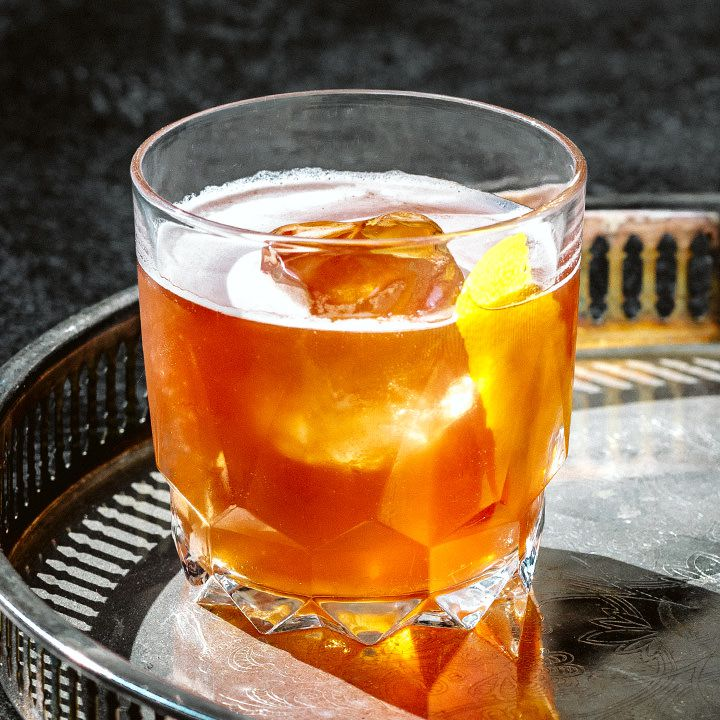 On a metal bar tray, a chunky rocks glass holds a bright orange cocktail. An ice cube pokes from the top of the drink, as does a thin slice of lemon peel.