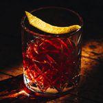 sazerac cocktail in a crystal-cut glass with a lemon peel garnish