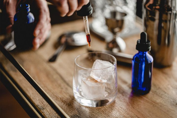 A man's hand drops a few dashes of bitters over three large cubes using a stopper. The cubes fill a modern rocks glass which sit on a chic bar tray next to another bottle of bitters.