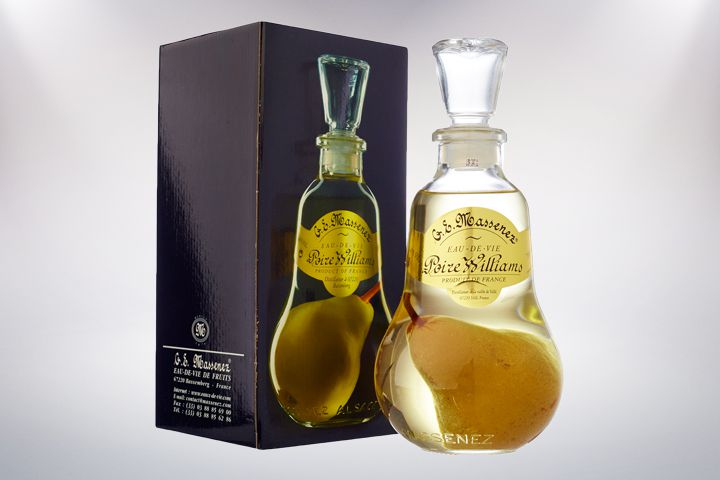 An elegantly curved bottle of clear pear eau-de-vie from G.E. Massenez, complete with a whole pear in it, sits next to a box with the bottle printed on it.