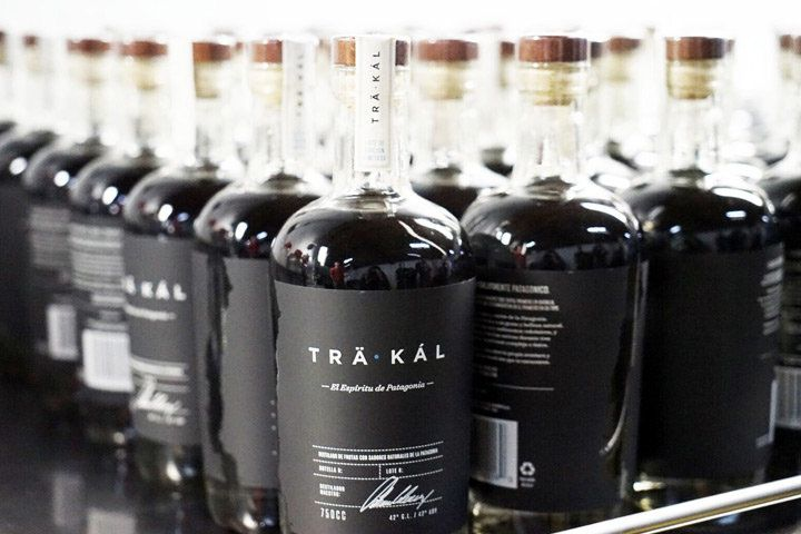 A metal shelf full of clear Trakal bottles with black and white labels and a dark-hued liquid inside
