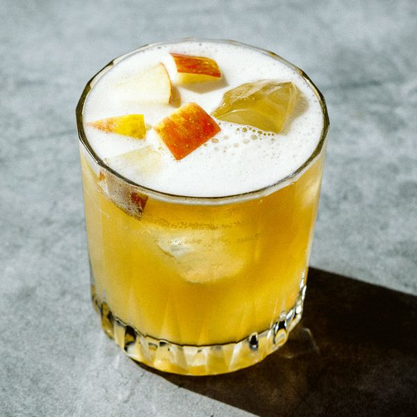 A faceted rocks glass rests on a polished concrete surface. The glass holds ice cubes and a golden yellow drink topped with white foam and some chunks of apples.