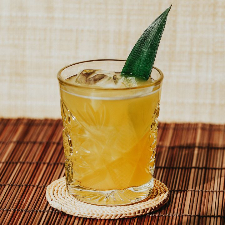 Ginger Smash cocktail with pineapple leaf, served on round, woven coaster