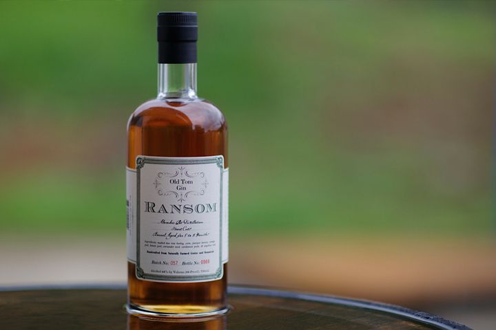 A bottle of amber-hued Ransom Old Tom Gin against a green outdoor background