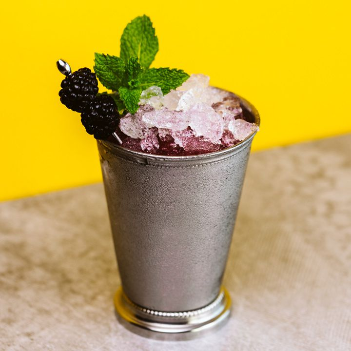 A silver julep cup is beaded with condensation. The cup holds a violet liquid, a pile of crushed ice, a sprig of mint, and two blackberries pierced on a silver pick. The drink sits on a tan surface with a bright yellow wall behind it.