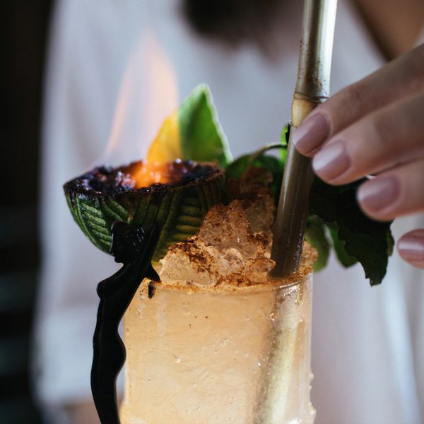 hand placing a bamboo straw in Storm the Beach, a cocktail served in a Tiki mug with flaming lime shell garnish