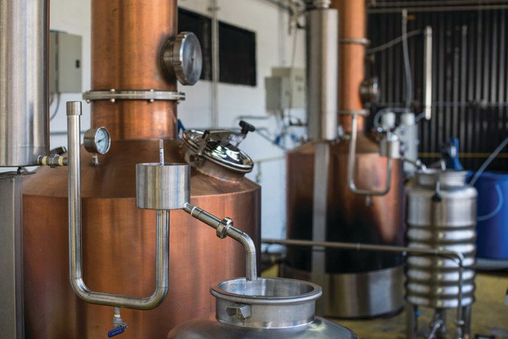 Two copper stills in a warehouse
