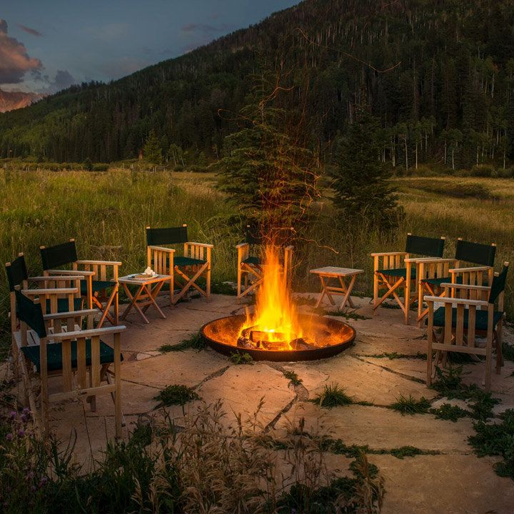 Dunton River Camp firepit with a tree-filled mountain in the background