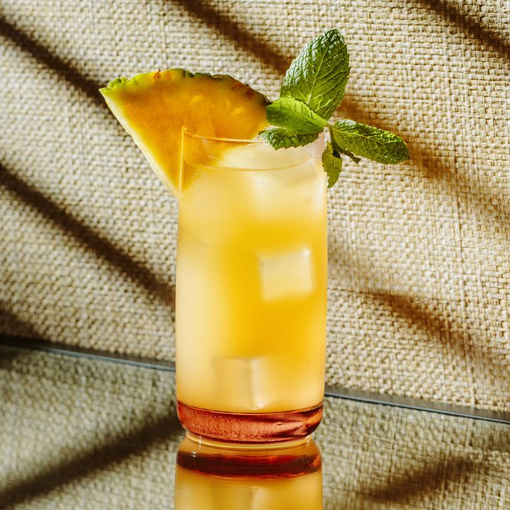 A Collins glass filled with bright yellow punch garnished with a pineapple slice and a sprig of fresh mint.