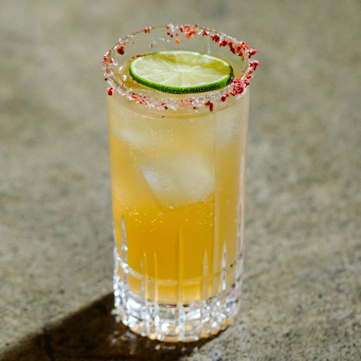 On a gray surface, a faceted high ball glass is filled with an orange-hued soda and a few ice cubes. Its rim is dusted with bright red flakes, and it's garnished with a single lime wheel.