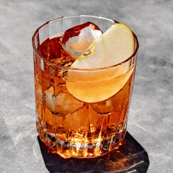 A beveled rocks glass with a reddish-brown stirred cocktail, three clear ice cubes, and a thin apple slice