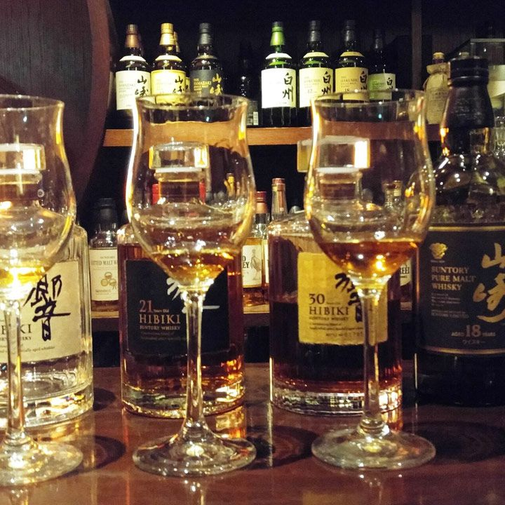 Hibiya Bar Whisky-S. Two tulip glasses are filled with a dram of whisky. Behind them are four bottles of Japanese whisky