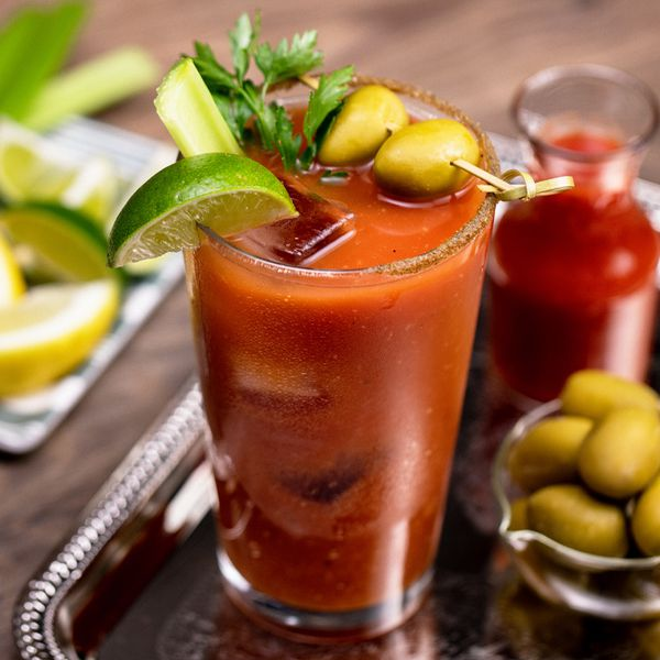 Bloody Mary cocktail on a tray with citrus and olives