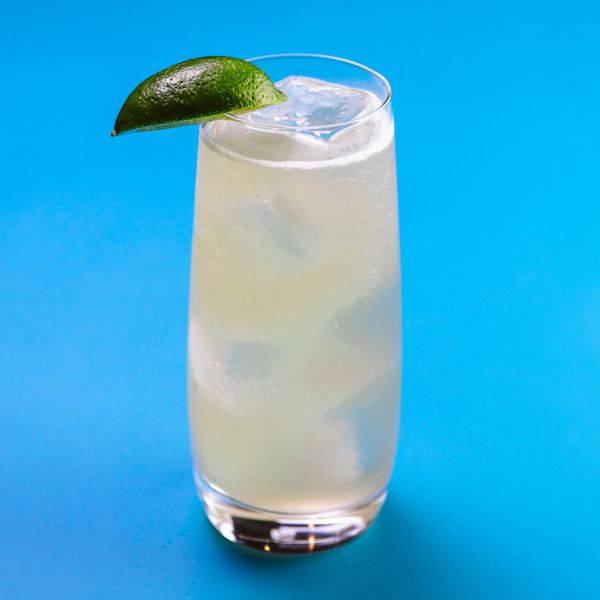 Mule cocktail in a Collins glass with ice, garnished with a lime wedge and set against a blue background