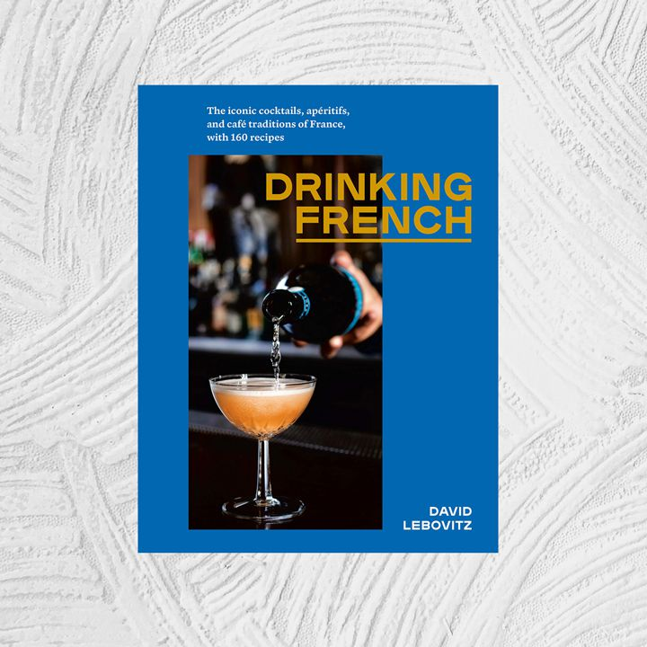 Drinking French: The Iconic Cocktails, Apéritifs, and Café Traditions of France, with 160 Recipes cover featuring a dark photograph of an orange cocktail in a coupette being topped with sparkling wine. Background behind offset image is a flat dark blue; text is white and orange