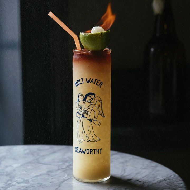 A tall highball glass sits on a marble table. It reads Holy Water Seaworthy, with a drawing of an angelic figure. It's filled with crushed ice and light brown drink, with a dark float on top. Atop that is a lime half with a burning sugar cube, as well as an orange bendy straw.