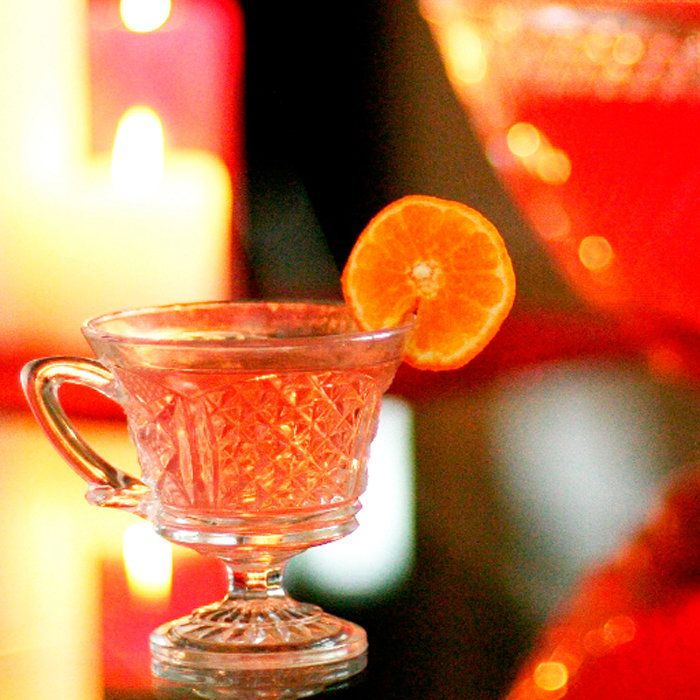 A chunky, detailed punch glass holds a pale, red-orange punch. It's garnished with an orange wheel. A punchbowl is in the background, out of focus.