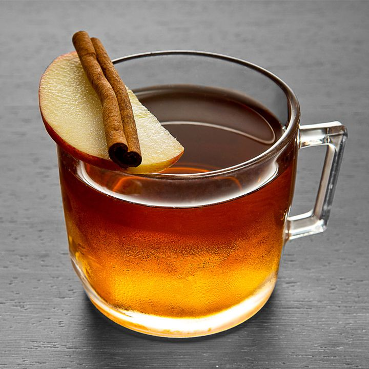 golden-brown Lights Out Punch cocktail in a glass mug with handle, garnished with an apple slice and cinnamon stick lying on the rim