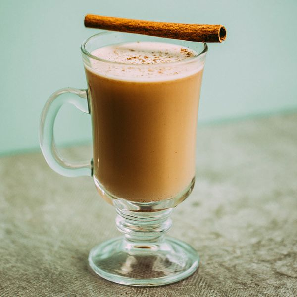 A glass mug holds a lush, golden-brown serving of Hot Buttered Rum. Its pale surface is flecked with nutmeg, and a cinnamon stick rests across the mouth of the mug. The background is pale blue, and the surface a light gray.
