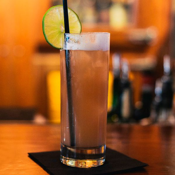 A traditional highball glass rests on a black cocktail napkin on a bar, the background hazy and indistinct. The drink is a dark brown, and garnished with a long black straw and a lime wheel.