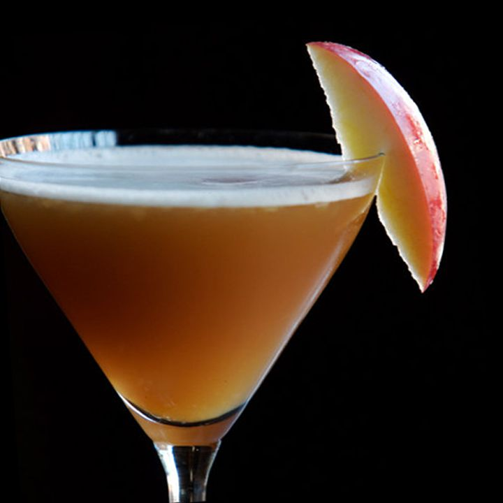 On a solid black background, a cocktail glass is filled with a dark brown drink, a thin layer of white foam resting on top. It's garnished with a sliver of apple.