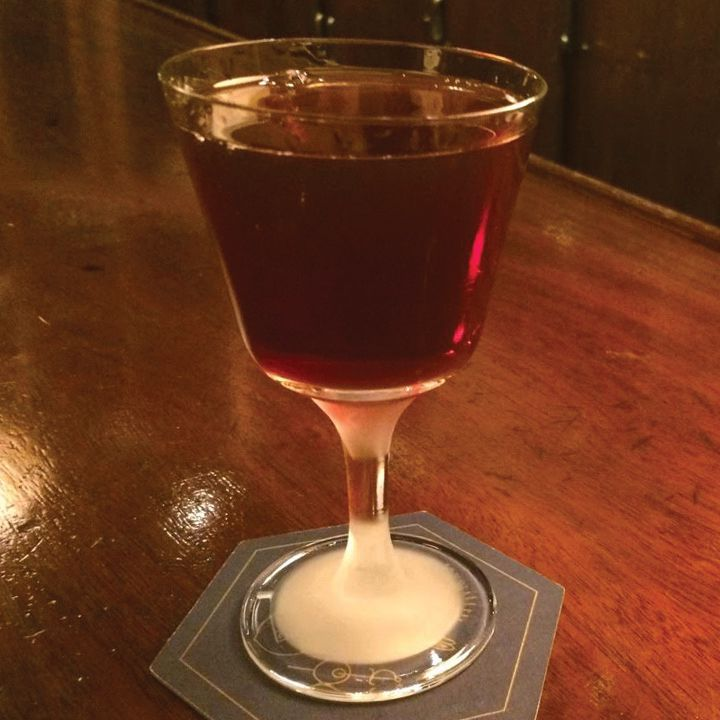 A stemmed rocks glass rests on a hexagonal coaster on a shiny wooden bar. The drink is dark red, and the stem is frosted over.