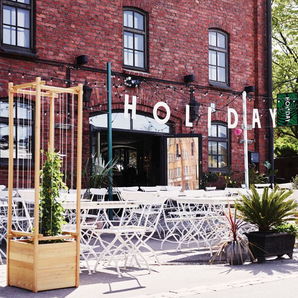 Holiday Bar exterior with white outdoor tables and chairs near a brick building