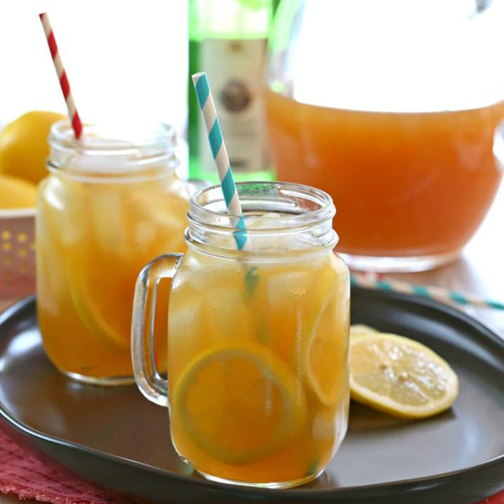 Two Mason jar mugs filled with peachy-hued sangria, ice, and citrus wheels