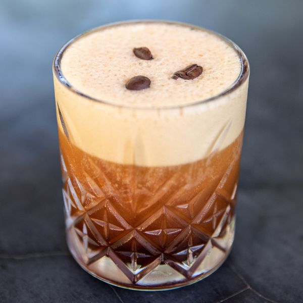 A dark brown, foamy cocktail in a faceted rocks glass sit at Chef's Table at La Zebra in Tulum, Mexico. Atop its foamy surface are three coffee beans