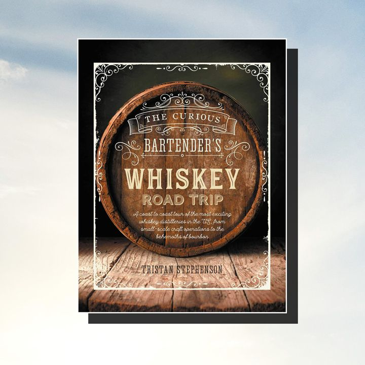The Curious Bartender's Whiskey Road Trip cover (white filigree and text overlaid on a barrel sitting on a wood floor with a dark gray wall behind it). Cover with drop shadow is set against a cloudy sky background