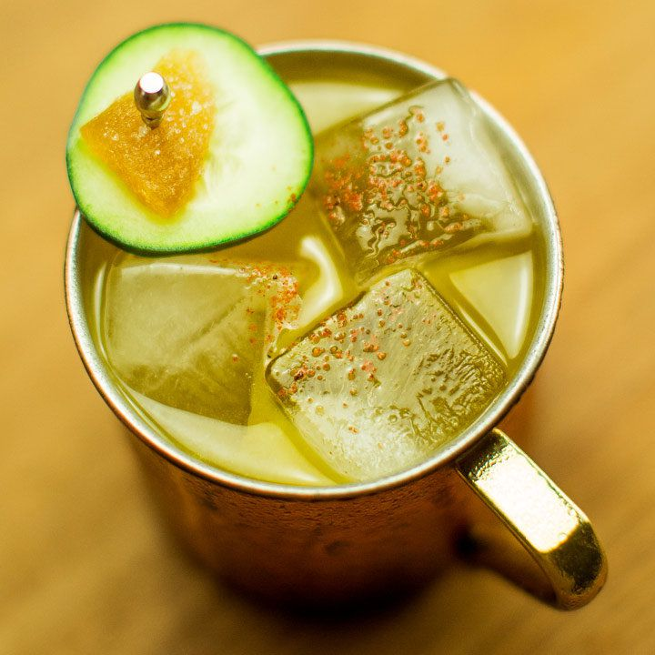 mezcal mule cocktail garnished with a cucumber slice and candied ginger