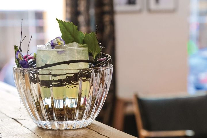 Lilla. e cocktail with leaf and flower garnish