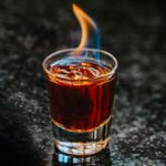 Flaming Dr. Pepper Shot served in a shot glass with a blue-and-orange flame